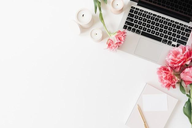 ノートパソコンと美しいピンクの牡丹のチューリップの花、白紙のシートカード、白のキャンドル。フラットレイ、上面図