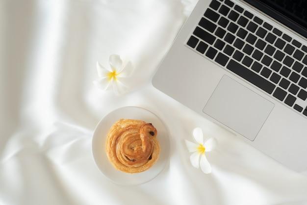 ノートパソコンと白い布の背景にパンと花オンライン学習の概念