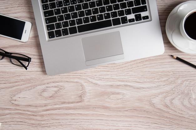 木製のテーブルの上のノートパソコンとコーヒーカップ