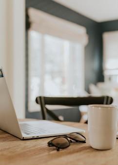 木製のテーブルの上のラップトップとコーヒーカップ