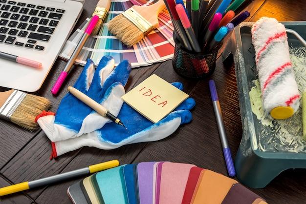 オフィスであなたのデザインの家のためのラップトップとカラーパレットのブラシと手袋。改修のためのツール