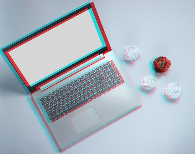 灰色の背景にラップトップとしわくちゃの紙のボール。ミニマルなビジネスコンセプト。グリッチ効果。上面図