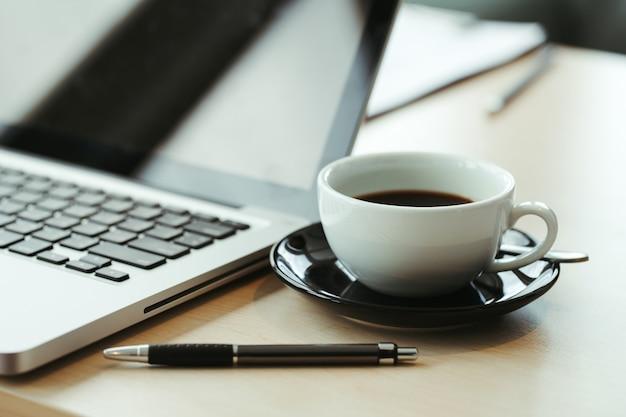 古い木製のテーブルの上のラップトップとコーヒーのカップ