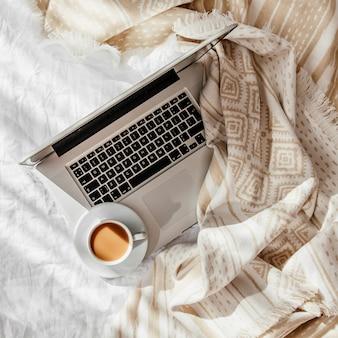 ノートパソコンとベージュの格子縞の白いベッドの上のコーヒーのカップ。自宅で働くというコンセプト。朝の光。ライフスタイルの概念