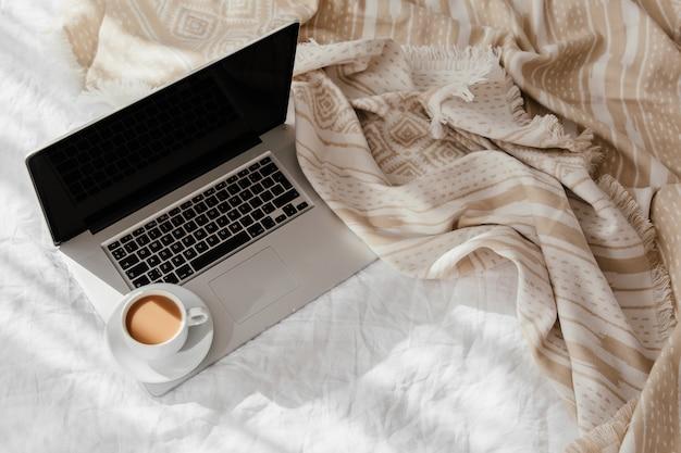 ノートパソコンとベージュの格子縞の白いベッドの上のコーヒーのカップ。自宅で働くというコンセプト。朝の光