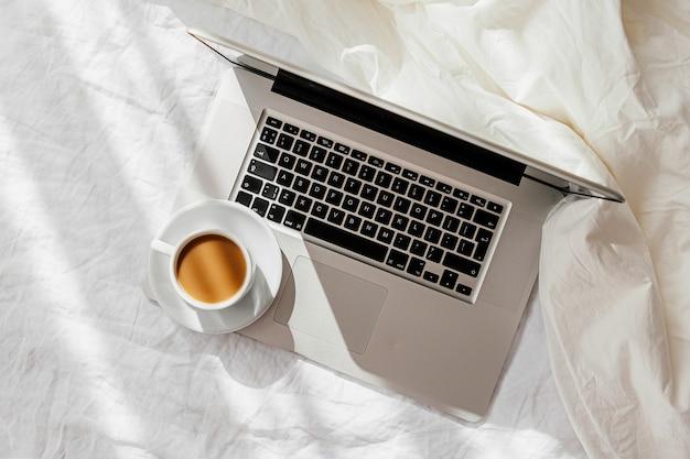 毛布と白いベッドの上のラップトップとコーヒーのカップ。自宅で働くというコンセプト。朝の光。ライフスタイルの概念
