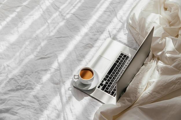 毛布と白いベッドの上のラップトップとコーヒーのカップ。在宅勤務のコンセプト。朝の光。ライフスタイルの概念