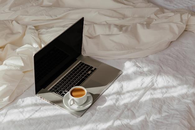 毛布と白いベッドの上のラップトップとコーヒーのカップ。自宅で働くというコンセプト。朝の光