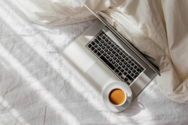 毛布と白いベッドの上のラップトップとコーヒーのカップ。在宅勤務のコンセプト。朝の光
