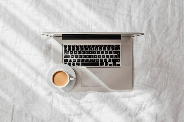 ノートパソコンと白いベッドの上のコーヒー。自宅で働くというコンセプト。朝の光。ライフスタイルの概念
