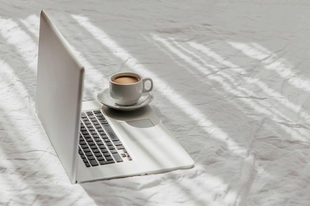 ノートパソコンと白いベッドの上のコーヒー。自宅で働くというコンセプト。朝の光