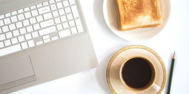 ノートパソコンとトースト、ビジネスコンセプトとコーヒーのカップ。