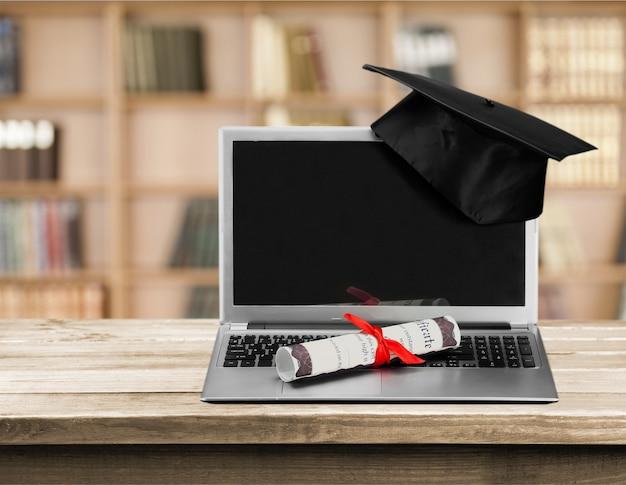 Ноутбук и свиток диплома на фоне
