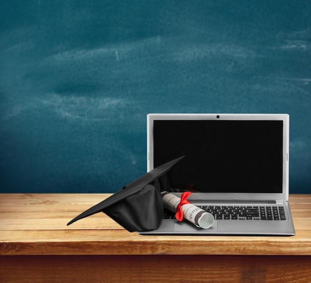 ノートパソコンと卒業証書は背景にスクロールします Premium写真