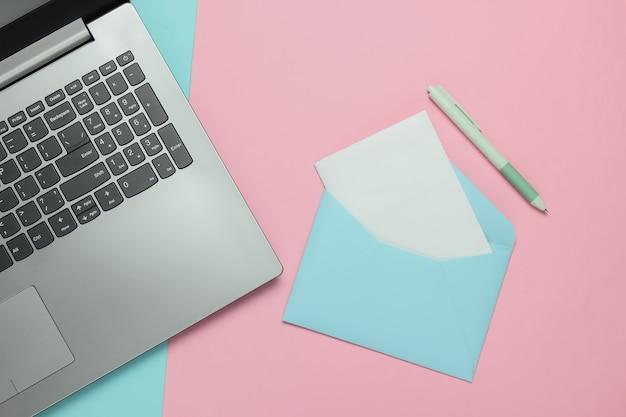 Ноутбук и конверт с письмом на розовом синем пастельном фоне. день святого валентина. вид сверху