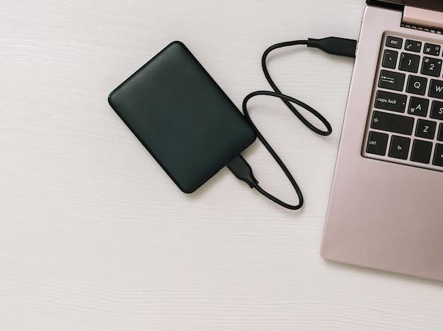 나무 테이블에 노트북 및 외장 하드 드라이브. 상단에서보기. 백업 스토리지의 개념. 평평하다.