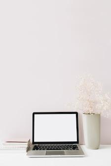 ピンクのラップトップと花の花束。正面図最小限のモダンなホームオフィスデスクワークスペース