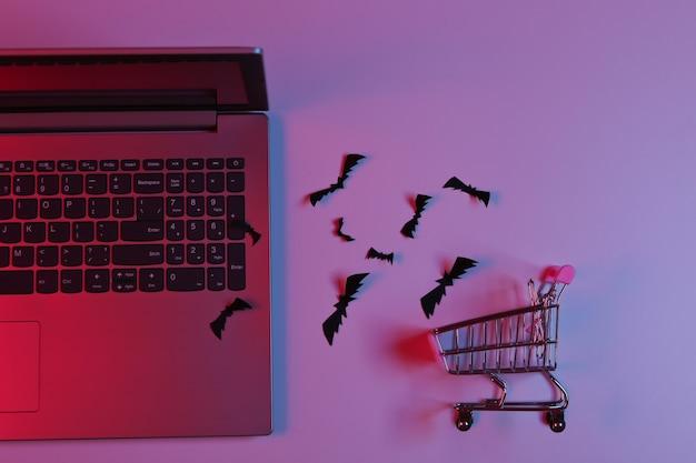 노트북과 날아다니는 종이는 파란색 분홍색 네온 불빛으로 쇼핑 트롤리로 박쥐를 잘라냅니다. 할로윈 테마