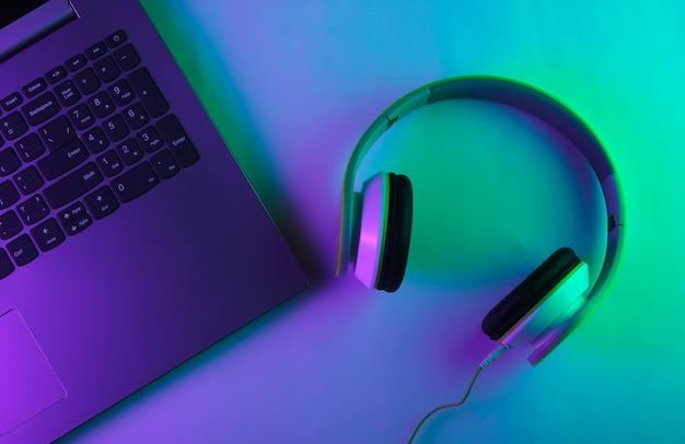 네온 녹색과 보라색 빛을 가진 노트북 및 헤드폰