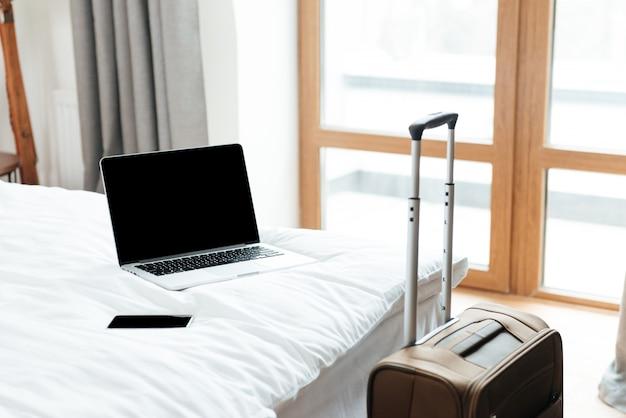 Ноутбук и мобильный телефон лежат на кровати в гостиничном номере