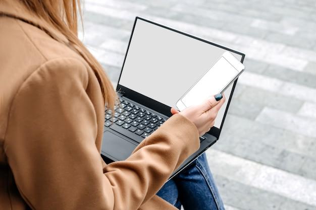 Макет ноутбука и мобильного телефона. молодая женщина использует ноутбук и держит смартфон с белым экраном, сидя на лестнице и глядя на пустой экран монитора возле офисного здания. скопируйте пространство для дизайна