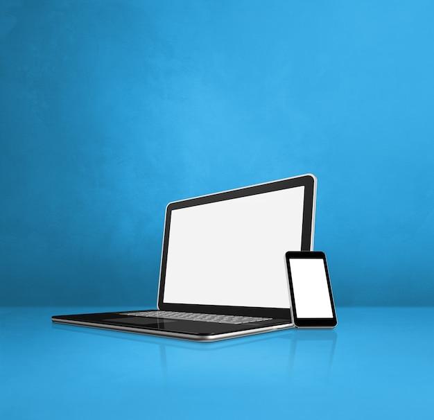 Ноутбук и мобильный телефон на синем офисном столе
