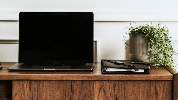木製のテーブルの上のラップトップとノートブック