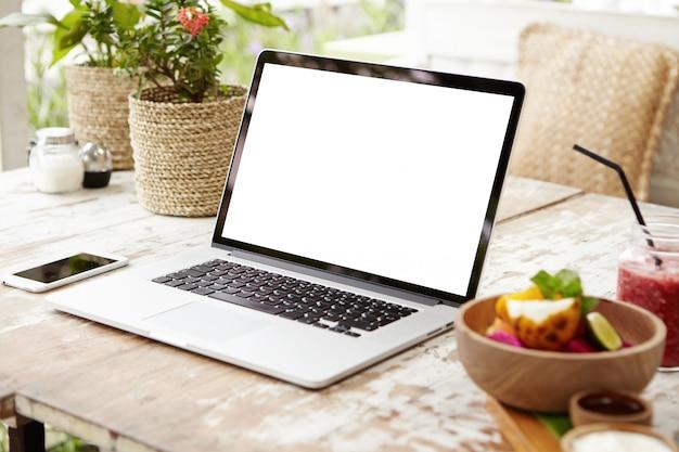 ワークスペース上のラップトップおよびその他の電子機器。現代のオープンラップトップと木製のテーブルにスマートフォンのビジネス職場。