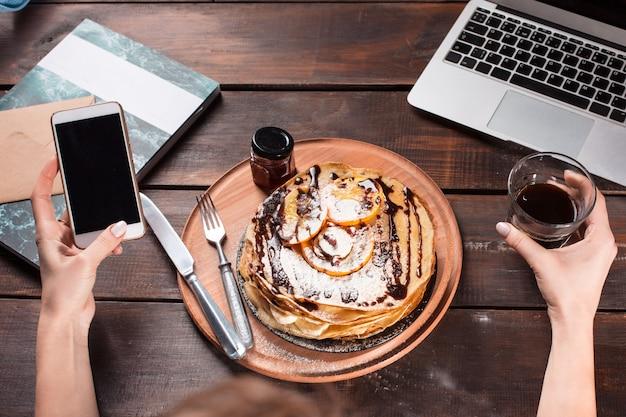 ノートパソコンとジュースとパンケーキ。ヘルシーな朝食