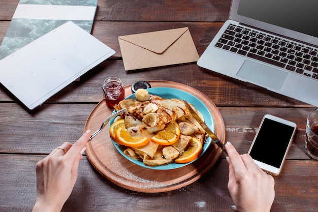 ノートパソコンとジュースと女性の手でパンケーキ健康的な朝食新鮮な自家製フレンチクレープ