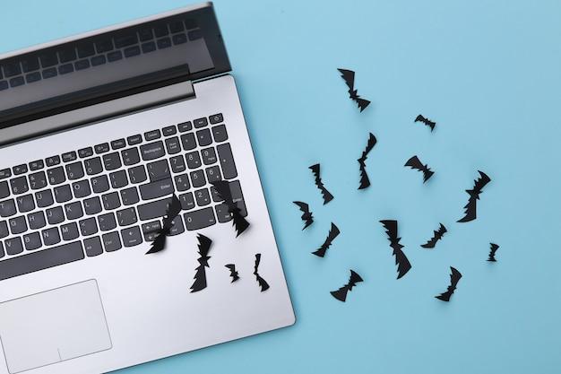 노트북과 종이는 파란색 배경에 박쥐를 잘라냅니다. 할로윈 테마입니다. 평면도