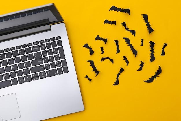 노트북과 종이는 노란색 배경에 박쥐를 잘라냅니다. 할로윈 테마입니다. 평면도