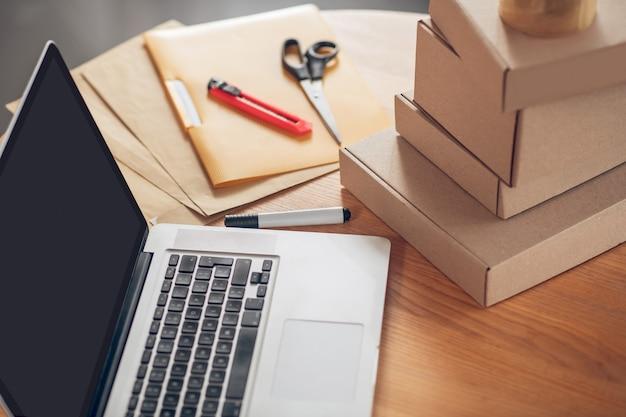 책상 위에 쌓인 노트북 및 제품 패키지