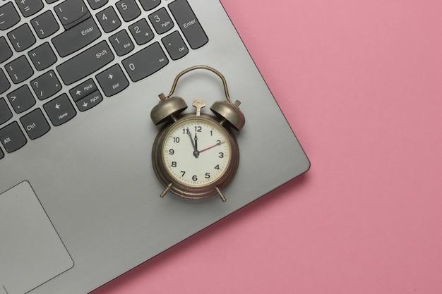 Ноутбук и ретро-будильник на розовом пастельном фоне. 11:55 утра. новый год. вид сверху