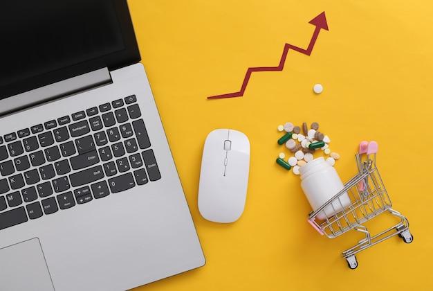 알약 한 병, 노란색 배경에 상승 화살표가 있는 노트북 및 쇼핑 트롤리. 온라인 쇼핑. 평면도. 플랫 레이