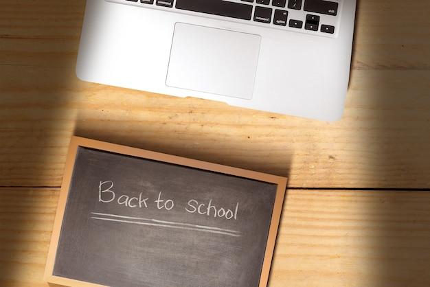 나무 배경에 학교로 돌아가라는 텍스트가 있는 노트북 및 작은 칠판. 학교 개념으로 돌아가기