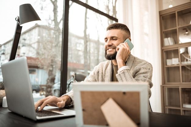 노트북과 스마트 폰. 근무 시간 동안 휴대 전화로 대화에 바쁜 집중 웃는 사업가