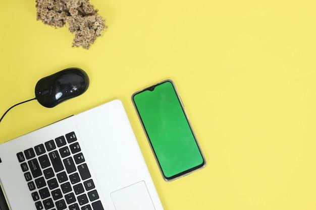 Ноутбук и смартфон на столе, изолированные на желтом фоне