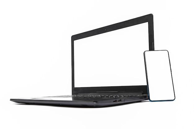 白い背景で隔離の空白の画面とノートパソコンとスマートフォン。