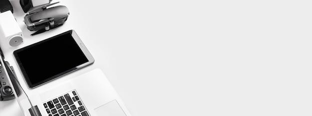 Ноутбук и планшет возле дрона на белом