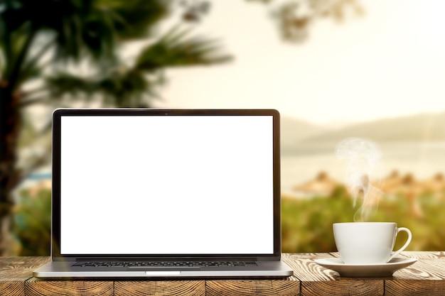 庭の木製の表面にノートパソコンとティーカップ