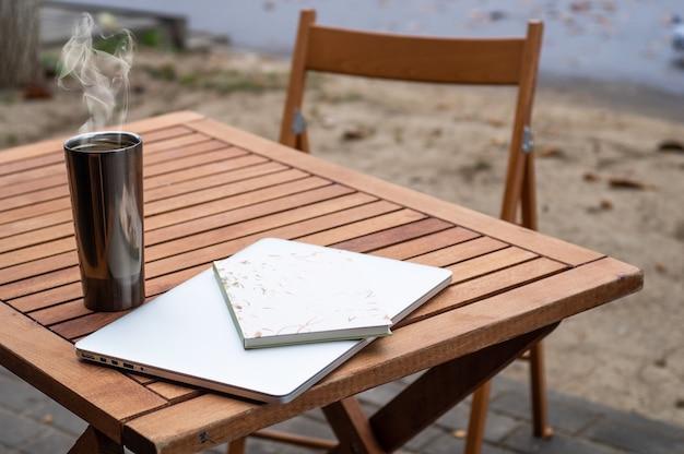 ノートパソコンとコーヒーのサーモカップはカフェの木製テーブルの上に立つ