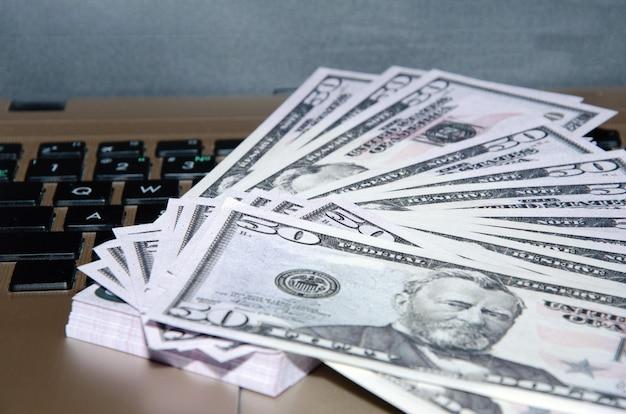 Ноутбук и долларовые деньги, компьютерный ноутбук и долларовые банкноты на деревянном фоне, технология с банкнотой в долларах сша,