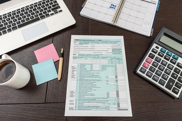 ノートパソコンと私たちのオフィスでの税務フォーム、企業会計。財務書類