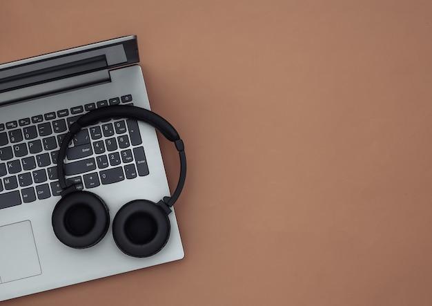Ноутбук и беспроводные стереонаушники на коричневом фоне. вид сверху. копировать пространство