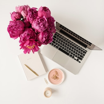 Laptop, beautiful pink peony tulip flowers bouquet and notebook on white table. flat lay, top view
