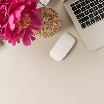 Ноутбук, букет цветов красивый розовый пион тюльпан на бежевом столе. плоская планировка, вид сверху