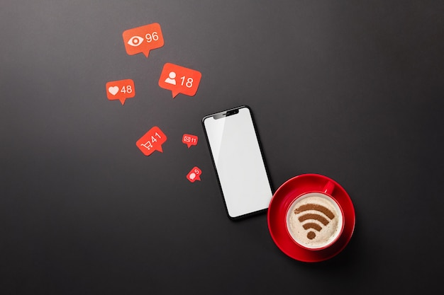 Laptop on a black desktop with a cup of coffee, a phone and a wi-fi sign, work in social networks. top view