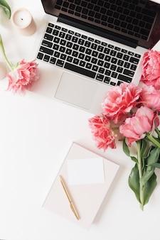 ラップトップ、白紙のシートカード、白いテーブルの上のピンクの牡丹のチューリップの花