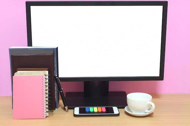 노트북 빈 화면과 책은 책상 위에 놓이고 복사 공간이 있습니다.